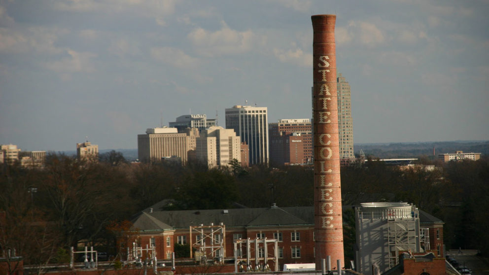 The Raleigh skyline is a backdrop to the State College smokestack on campus in 2004. (